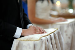 Groom's hands close-up during church ceremony. Groom's hands on the pillow close-up during wedding church ceremony Royalty Free Stock Image