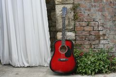 Groom's red and black guitar leaning against the wall on the wed