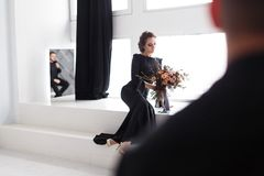 Groom`s reflection in mirror. Bride sitting on stairs in white studio.  royalty free stock images