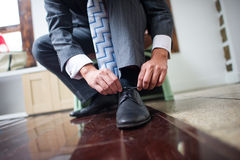 The groom's shoes. The groom bent over to tie his shoe Royalty Free Stock Photography