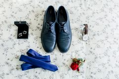 Groom`s shoes and cufflinks, blue tie, wristwatch, boutonniere on a light background. Wedding concept. Artwork, soft focus Royalty Free Stock Photography