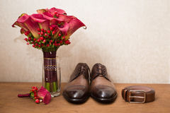 Groom`s shoes and wedding flowers Stock Photos