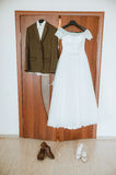 Groom's suit and bride's dress, wedding outfits for couple, hanging on the rack Stock Photos