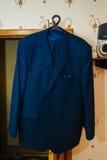 Groom's suit hanging on the door frame Stock Photos