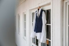 Groom`s suit hanging on a white wall stock image