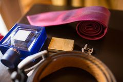 The groom`s wedding accessories. Blue perfume and cigarette lighter in focus, leather belt and red necktie. Blue perfume and cigarette lighter in focus, leather Royalty Free Stock Images