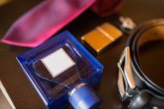 The groom`s wedding accessories. Blue perfume in focus, leather belt and red necktie. Blue perfume in focus, leather belt and red necktie. The groom`s wedding Stock Photography