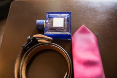The groom`s wedding accessories. Blue perfume in focus, leather belt and red necktie. Details Royalty Free Stock Image