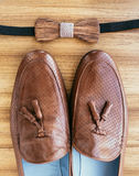 Groom's wedding accessories. Brown shoes and wooden bow-tie. On table Stock Photos