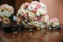 Groom`s wedding accessories. Shoes bouquet of flowers, cufflinks, wedding boutonniere and a belt. Groom`s wedding accessories. Shoes bouquet of flowers Stock Images