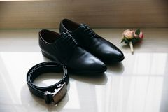 Groom`s wedding accessories. Shoes and wedding boutonniere and a belt.  Stock Photos