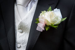 Groom's white boutonniere flower and suit details. White boutonniere flower from groom's suit at a wedding Royalty Free Stock Photography