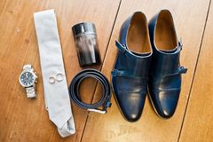 Groom`s white tie, silver watch, black leather belt, perfume and. A pair of wedding boots Royalty Free Stock Image