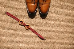 Groom`s bow tie and shoes on the floor. Groom`s wooden bow tie and brown leather shoes on the floor Stock Image