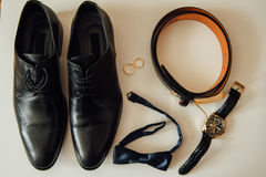 Groom set clothes. Wedding rings, shoes, cufflinks and bow tie Stock Photos