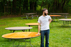 Groom Setting Up Wedding Tables. Groom wearing a white t-shirt setting up tables on his wedding day outdoors Royalty Free Stock Image