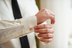Groom in a shirt and tie in the morning wears cufflinks Royalty Free Stock Photos