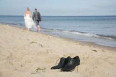 Groom' shoes on the beach. Just married couple walking on the seashore with focus on the man's shoes Stock Photography