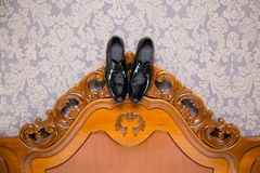 Groom shoes hanging on headboard Stock Photos
