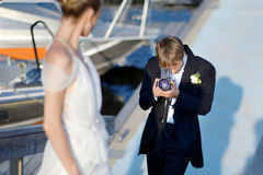 Groom shooting his bride with an old camera Stock Photos