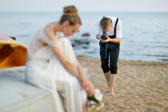 Groom shooting his bride with an old camera Stock Photography