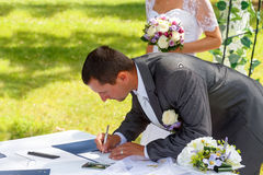 Groom signing certificate in park Stock Photos