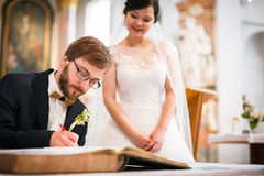 Groom signing the Contract of his life. Portrait of a young wedding couple on their wedding day Royalty Free Stock Images