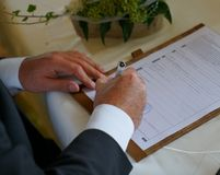 Groom signing for marriage in civil registry office stock photo