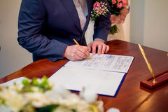 Groom signing marriage license Royalty Free Stock Photography
