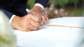 Groom signing the wedding register. Royalty Free Stock Photography