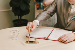 Groom signs documents in registry office. The groom signs the documents in the registry office Stock Photography