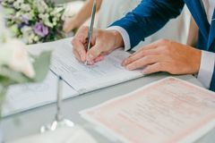 The groom signs the marriage registration documents. Young couple signing wedding documents. Man signs the documents Royalty Free Stock Images