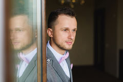 Groom silhouette reflected in the window. Portrait of young man wearing bow tie and suit. Groom silhouette reflected in the window. Elegant young fashion man Stock Images