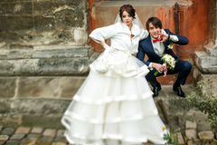 Groom sit squatting on a stone footstep behind a bride Stock Images