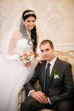 The groom sits in a chair and the bride stands near groom in the room stock photo