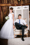 The groom sits in a chair and the bride stands near groom in the room royalty free stock photography