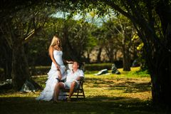 Groom sits on a lawn on a chair in the middle of tropical trees, and the bride stands next to him stock photo
