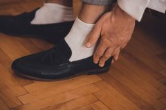 The groom sits on the wedding mornings stock photos