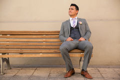 Groom sitting on a bench. Full length portrait of a Latin groom sitting on a bench outside and looking towards copy space Royalty Free Stock Images