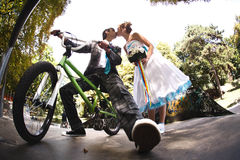 Groom sitting on the bicycle is kissing his wife Royalty Free Stock Images