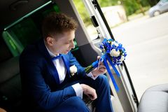 Groom sitting in car and holding wedding bouquet Stock Photos