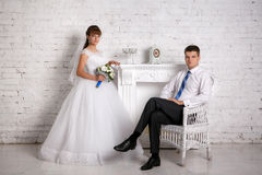 Groom is sitting in a chair and bride is standing near the fireplace Royalty Free Stock Photo