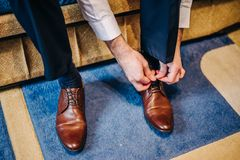 The groom is sitting on the couch, his hands are lacing brown leather shoes. On the wedding day Stock Image