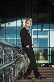 Groom sitting on modern handrails. Handsome groom sitting on modern metal handrails holding hands in pockets of elegant suit stock photo