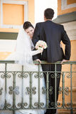 Groom sitting on railing while bride hugging him Stock Image