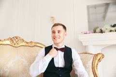 Groom sitting on the sofa waiting for the bride on his wedding day. at wedding tuxedo smiling and waiting for bride.Elegant man Stock Photography