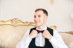 Groom sitting on the sofa waiting for the bride on his wedding day. at wedding tuxedo smiling and waiting for bride.Elegant man Stock Image