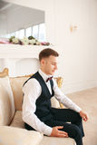 Groom sitting on the sofa waiting for the bride on his wedding day. at wedding tuxedo smiling and waiting for bride.Elegant man Royalty Free Stock Photos