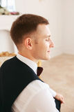 Groom sitting on the sofa waiting for the bride on his wedding day. at wedding tuxedo smiling and waiting for bride.Elegant man Stock Photos