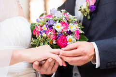 Groom slipping ring on finger of bride at wedding Stock Photography
